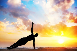 Yoga vasisthasana side plank pose by woman in silhouette with sunset sky background.